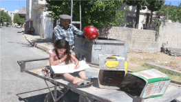 Babasının çöpten topladığı kitapları okuyor
