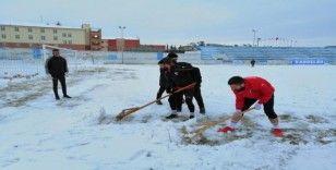 Sporcular çim sahada kar küredi