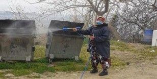 Kadın muhtar mahallesini dezenfekte ediyor
