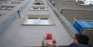 Anneler günü çiçeğini balkondan uzattığı sepetle aldı