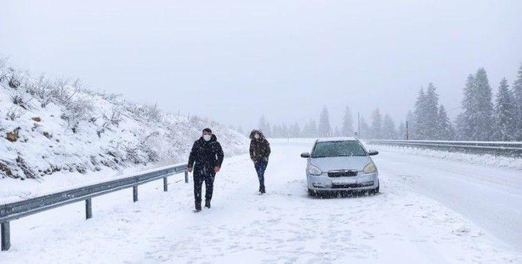 Kar yağışı nedeniyle yolda kalan araçlarını iterek çıkarmaya çalıştılar