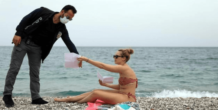 Konyaaltı sahilinde polisler, kısıtlamadan muaf olan turistlere pasaport ve kimlik denetimi yaptı