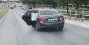 Eşya yüklü otomobilin arka kapısı açık haldeki yolculuğu kamerada