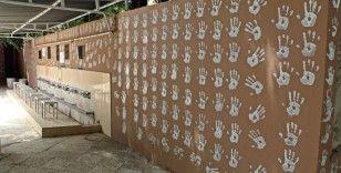 Boya kovasına ellerini batırıp caminin duvarlarını el izleriyle doldurdu